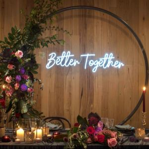 Better Together On-Trend LED Neon Wedding Light shown hung from a floral arch behind the to table - photo from CustomNeon.co.uk