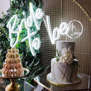 Large Bride to Be Wedding Sign in Bright LED Neon shown mounted on wire mesh behind the wedding cake - photo from CustomNeon.co.uk