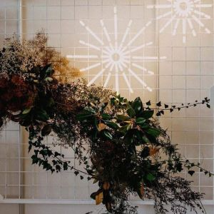 Christmas Star LED Neon Light shown on a frame with seasonal florals - photo from CustomNeon.co.uk