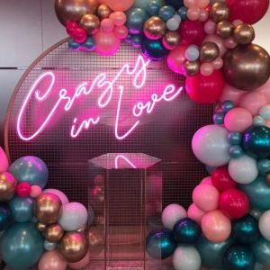 Crazy In Love Wedding Sign in brilliant LED neon flex shown in pink with balloons - photo from CustomNeon.co.uk