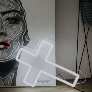 LED neon cross shown in white against a painting - photo from CustomNeon.co.uk