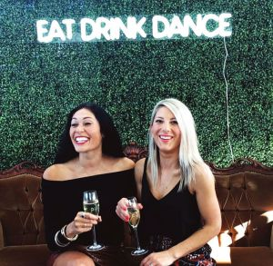 EAT DRINK DANCE Portable LED Neon Light Sign shown on a green wall at an Event - photo from CustomNeon.co.uk
