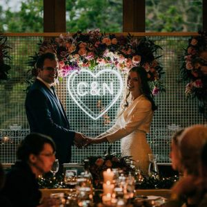 Beautiful LED neon heart light personalised with the bride & groom's initials. Shown here on a mesh background during the wedding reception - Custom Neon