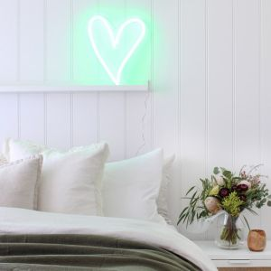 A little love heart in green shown as bedroom decor, on a shelf against a white wall - photo from CustomNeon.co.uk