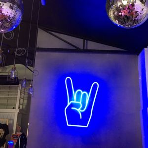 Rock On Emoji LED Neon Sign shown in blue, wall mounted in a fashion store - photo from CustomNeon.co.uk