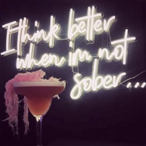 I Think Better When I'm Not Sober LED neon bar sign shown with cocktail - photo from CustomNeon.co.uk
